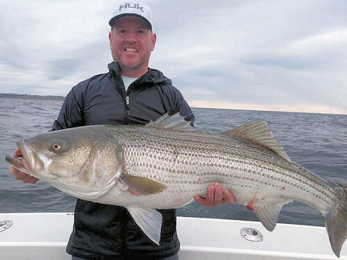 Fish Trap customer holding huge striped bass
