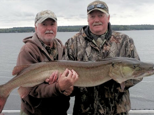 Two anglers holding muskie