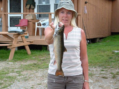 Lady holding up trout.